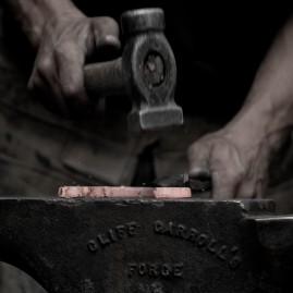 Blacksmith shaping a hot horseshoe